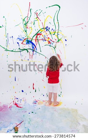 Full Length Shot of a Young Little Kid Painting Something Abstract on White Big Wall Using Different Colors. - stock photo