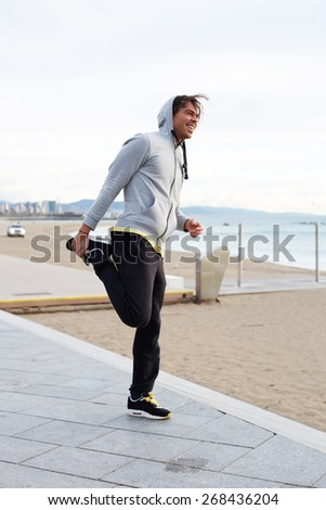 Full length shot of a young male jogger stretching before his run, male jogger doing stretching exercise while standing on seaside listening to music on headphones - stock photo