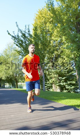 Full length shot of a young man running outdoor in the park.