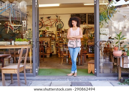 Full length shot of a young mixed race woman happily standing in the doorway of her trendy coffee shop - stock photo