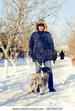 Full Length Shot of an Adult Man in Winter Outfit with his Dog Standing at the Snow and Looking at the Camera. - stock photo