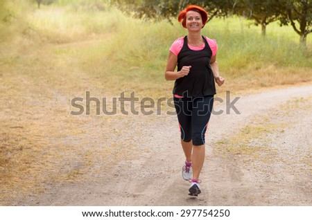 Full Length Shot of an Athletic Middle Aged Redhead Woman Jogging Along the Pathway and Smiling at the Camera. - stock photo