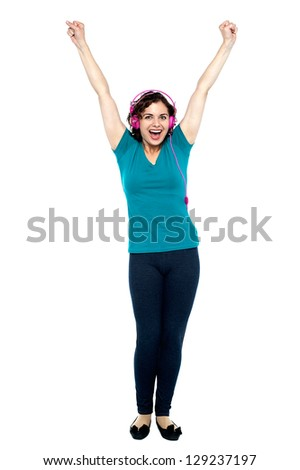 Full length shot of an euphoric music enthusiast throwing up her arms.