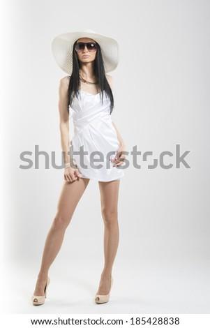 Full length shot of beautiful Caucasian woman wearing short white dress, sunglasses and large white hat - stock photo