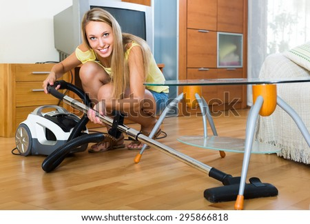 Full length shot of blonde young woman cleaning with vacuum cleaner at home - stock photo
