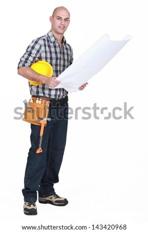 full-length shot of carpenter consulting blueprints - stock photo