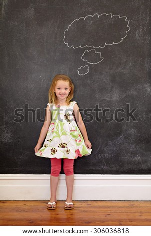 Full length shot of cute young girl in front of chalkboard with a thinking bubble, She is holding her dress looking at camera smiling at home. - stock photo
