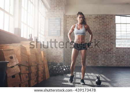 Full length shot of determined fitness woman walking in the crossfit gym. Muscular sportswoman warming up before a intense workout. - stock photo