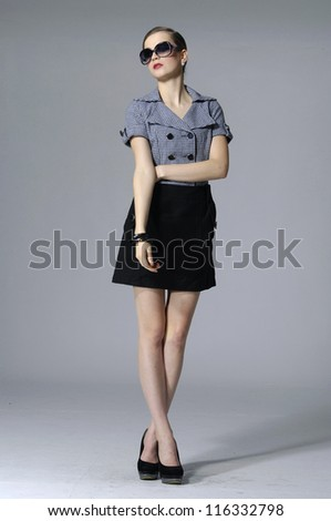 full length shot of fashion model in sunglasses posing on gray background - stock photo