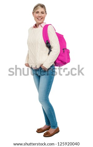 Full length shot of fashionable college student in warm clothing posing with pink backpack. - stock photo