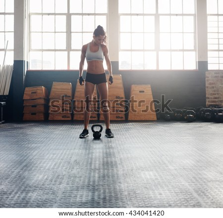 Full length shot of fit and strong woman standing in crossfit gym. Tough fitness female model with kettle bell on floor. - stock photo