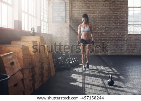 Full length shot of fitness woman walking in the gym with kettle bell on floor. Female athlete warming up before a intense fitness training. - stock photo