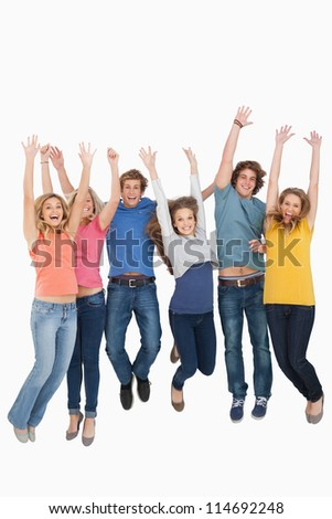 Full length shot of friends celebrating and jumping in the air while looking at the camera - stock photo