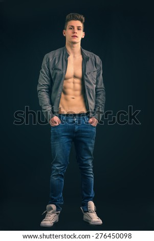 Full length shot of handsome athletic young man wearing leather jacket open on naked torso, muscular pecs and abs - stock photo