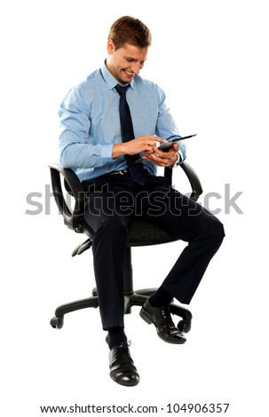 Full length shot of seated entrepreneur using electronic tablet