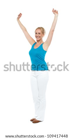 Full length shot of successful woman posing with raised arms