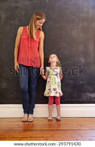 Full length shot of sweet little girl standing with her mother at home. Mother and daughter looking at each other against a wall, indoors. - stock photo