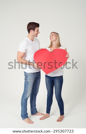 Full Length Shot of Sweet Young Couple Holding Red Heart Object with Copy Space on White Background Inside the Studio.
