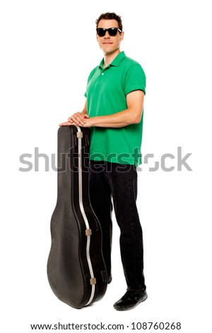 Full length shot of trendy young man posing with guitar case over white - stock photo