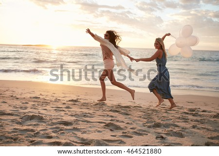 Full length shot of two young women running on the beach with balloons. Female friends having fun on the sea shore.