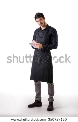 Full length shot of young chef or waiter posing, wearing black apron and shirt, writing order on notepad, isolated on white background - stock photo