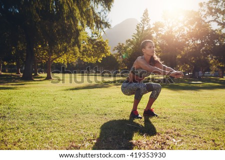 Full length shot of young woman practicing squats in park. Horizontal shot of a young woman exercising outdoors on a nice summer day. - stock photo