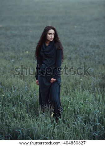 Full length side fashion portrait of young beautiful brunette girl in black dress. Posing in grass and flowers. Long black hair. Outdoor. Summer.