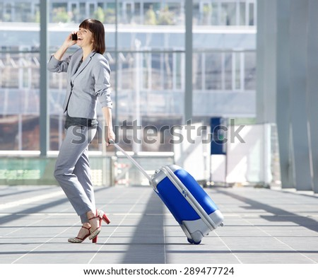 Full length side portrait of a happy business woman walking with suitcase and talking on mobile phone at airport - stock photo