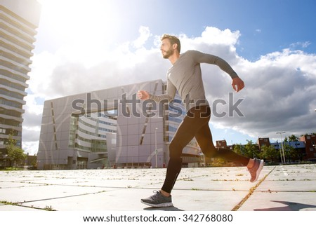 Full length side portrait of a man running in the city - stock photo