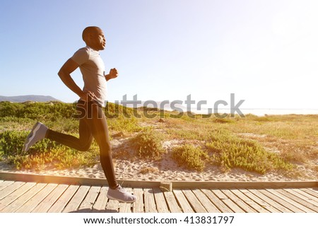 Full length side portrait of fitness man running on the boardwalk at the beach on a bright sunny day
