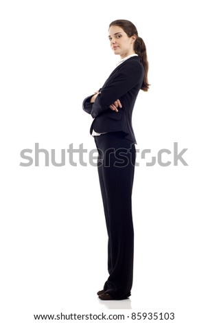 Full length, side view of a confident young business woman standing with folded hands isolated over white background