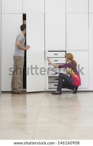 Full length side view of a couple looking in wardrobe in empty apartment - stock photo