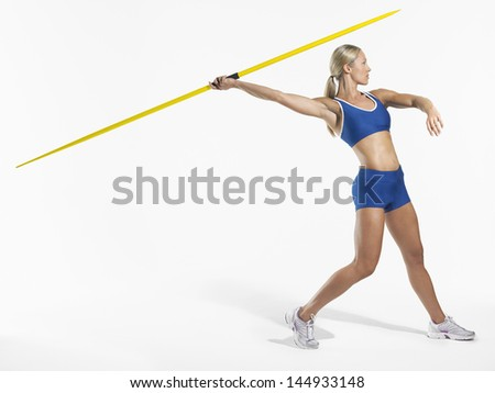 Full length side view of a female athlete preparing to throw javelin against white background - stock photo