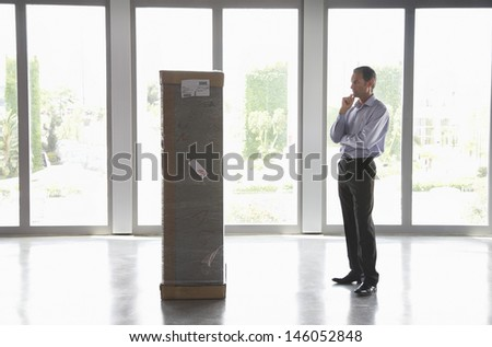 Full length side view of a man with hand on chin observing package in empty office - stock photo
