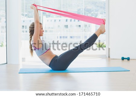 Full length side view of a sporty young woman with exercise band in fitness studio - stock photo