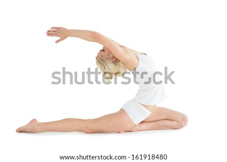 Full length side view of a toned young woman stretching hands backwards over white background - stock photo