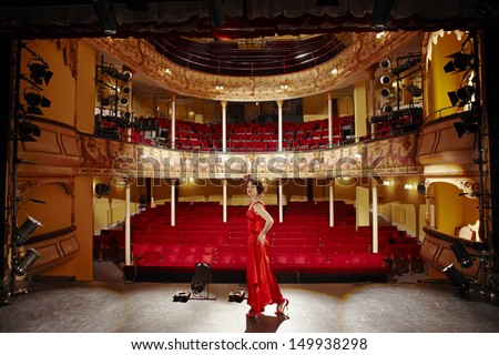 Full length side view of a woman in red gown on stage floor - stock photo
