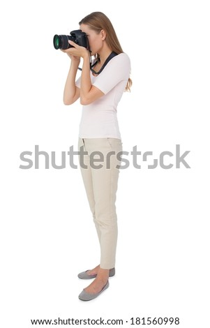 Full length side view of a woman with camera over white background - stock photo