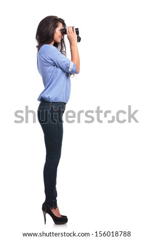 full length side view of a young casual woman looking away through binoculars. on white background