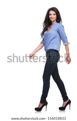 full length side view of a young casual woman walking forward while looking into the camera. on white background