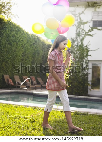 Full length side view of a young girl walking with bunch of balloons in lawn - stock photo