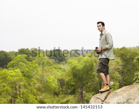 Full length side view of a young man on rock with binoculars looking at view
