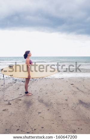 Full length side view of a young woman carrying surfboard on the beach