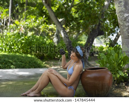 Full length side view of a young woman in bikini pouring water on self
