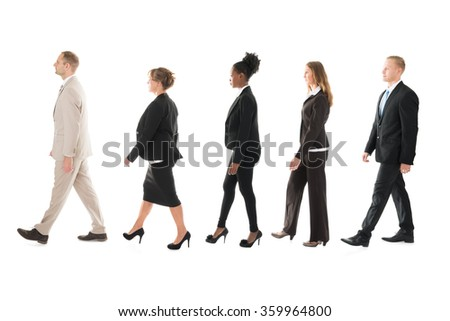 Full length side view of business team walking in row against white background - stock photo