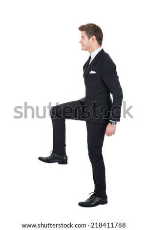 Full length side view of businessman climbing imaginary steps against white background - stock photo
