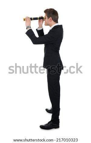 Full length side view of businessman looking through handheld telescope against white background