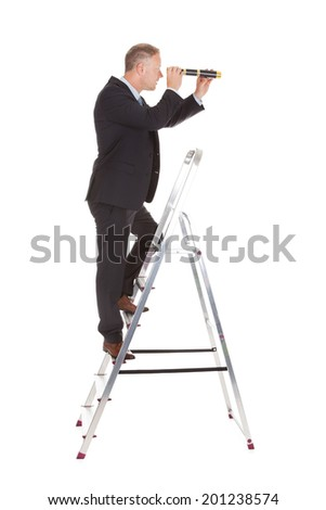 Full length side view of businessman on ladder looking through telescope over white background - stock photo