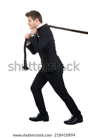 Full length side view of businessman pulling rope against white background