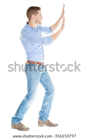 Full length side view of businessman pushing invisible wall against white background